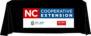 A black table cover illustration displaying the N.C. Cooperative Extension logo.