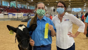 A female 4-H'er stands with her dairy steer and North Carolina Cooperative Extension 4-H Agent Holly Jordan during the 2020 WNC Livestock Expo.
